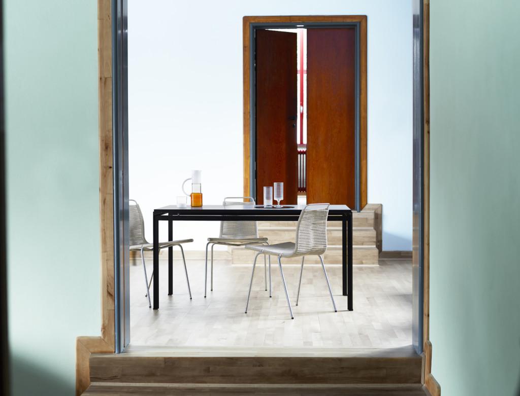 Både spisestolen PK1 i rustfritt, krombelagt eller svart pulverlakkert stål med naturfarget eller svart flaggline, og professor- og elevbordene med bordplate i laminat, vil fra i høst være tilgjengelige i butikkene. (Foto: Carl Hansen & Søn)
